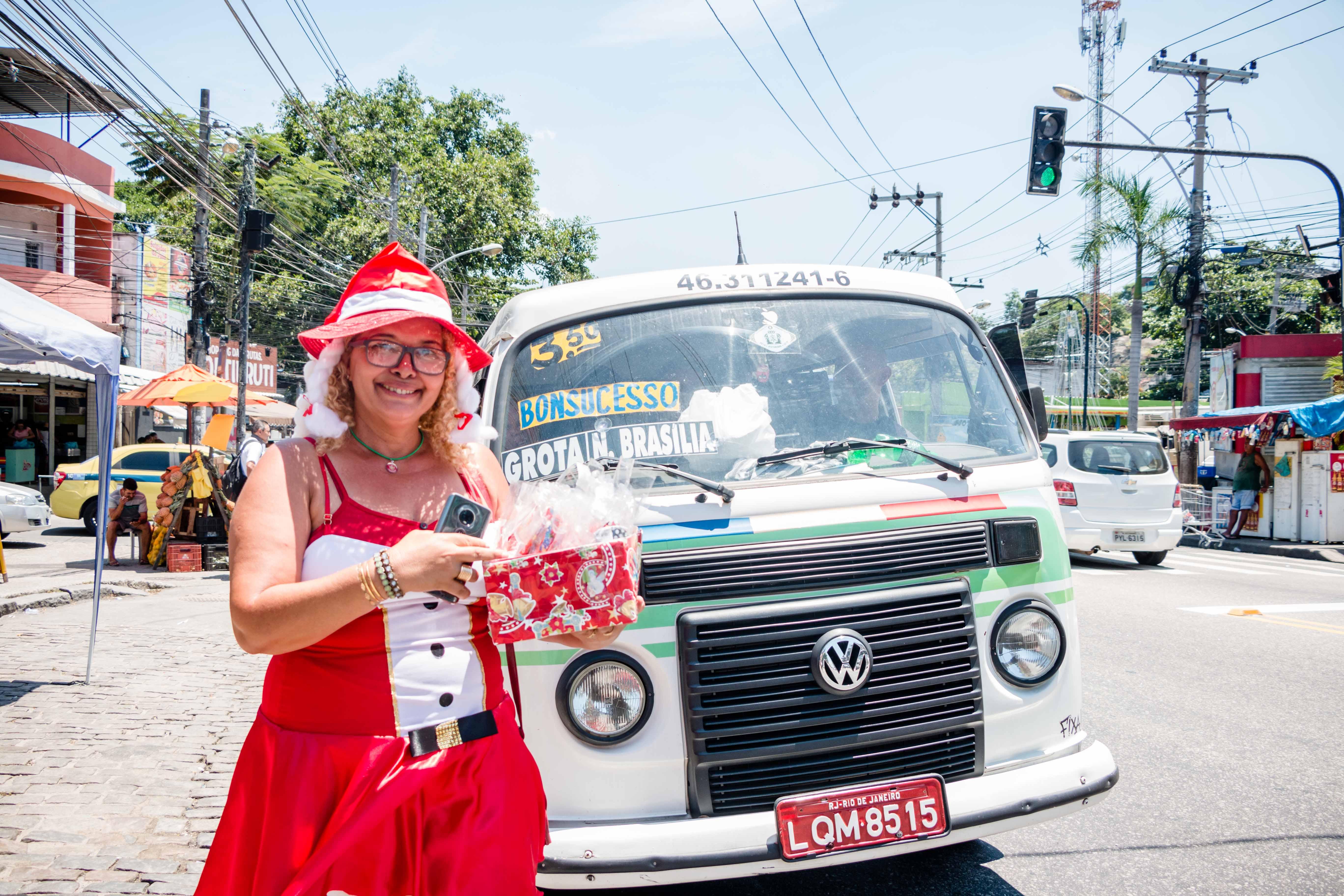Mamãe Noel do Complexo do Alemão leva alegria aos moradores em ponto de ônibus